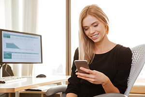 Woman sitting at table smiling at her cell phone